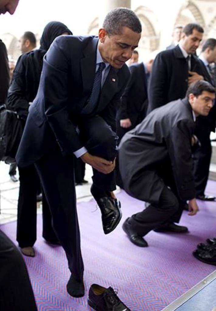 Obama removing his shoes at a mosque in Turkey in preparation to lift his ass in prayer to Allah, which he memorized when he attended a madrassa in Indonesia