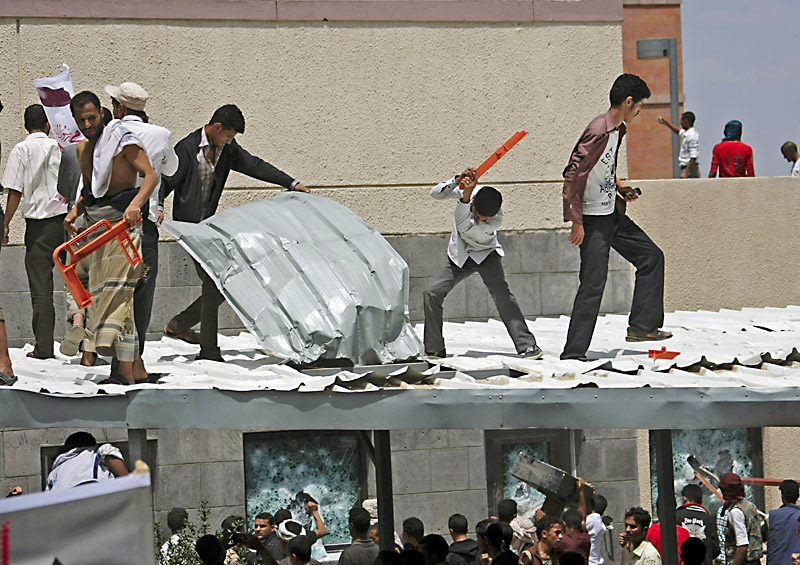 Yemeni protesters try to break through the roof of the US embassy. No security in sight.