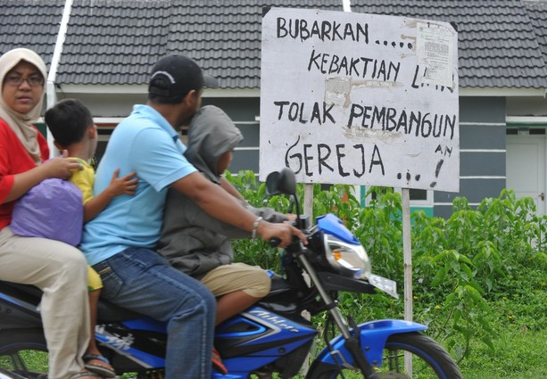 Residents on a motorcycle ride past a placard that reads 'Dismiss illegal Christian services, reject the church project' in front of a piece of land owned by a Christian congregation from the Filadelfia Batak Christian Protestant church