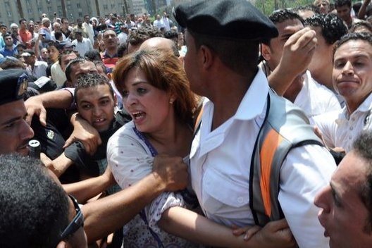 Woman in street hangs onto police for protection from Morsi's gangs