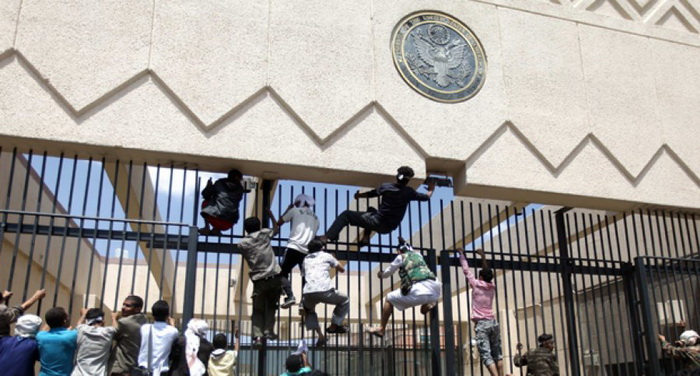 Angry Yemenis scaling the gate at the US Embassy in Yemen in protest of the anti-Islam film