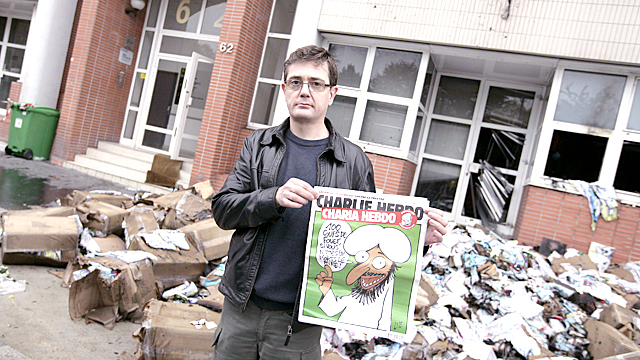he Charlie Hebdo's publisher, known only as Charb, shows a special edition of French satirical magazine Charlie Hebdo on November 2, 2011 in Paris, in front of the magazine's offices which were destroyed by a petrol bomb attack