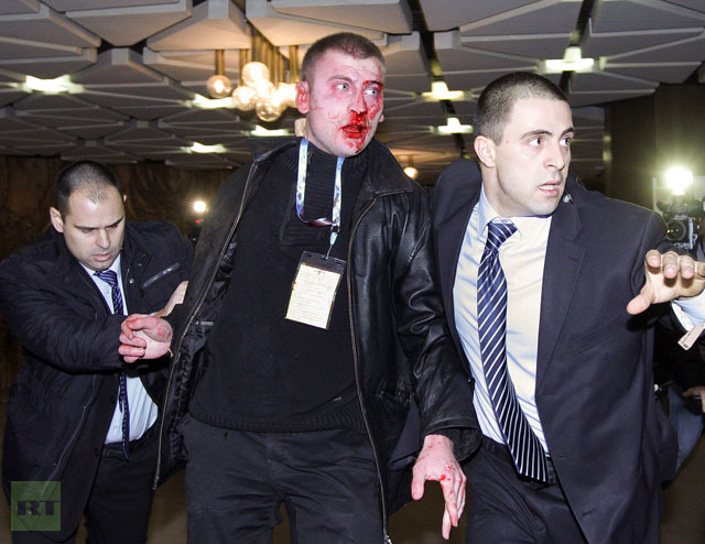 Bulgarian security officers escort a bloodied 25 year old man after he attacked Ahmed Dogan