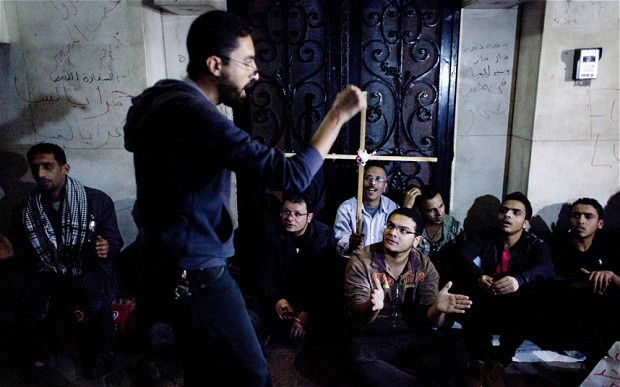 Egyptians by the entrance of the Libyan embassy protest for the death of Egyptian Christian Ezzat Atallah at a Libyan prison