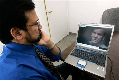 """Sohail Mohammed, an immigration lawyer who represented detainees caught in the post-Sept. 11 furor, watches the Fox series '24' at his office in Clifton, N.J. """"Somewhere, some lunatic out there watching this will do something to an innocent American Muslim because he believes what he saw on TV,"""" Mohammed said."""