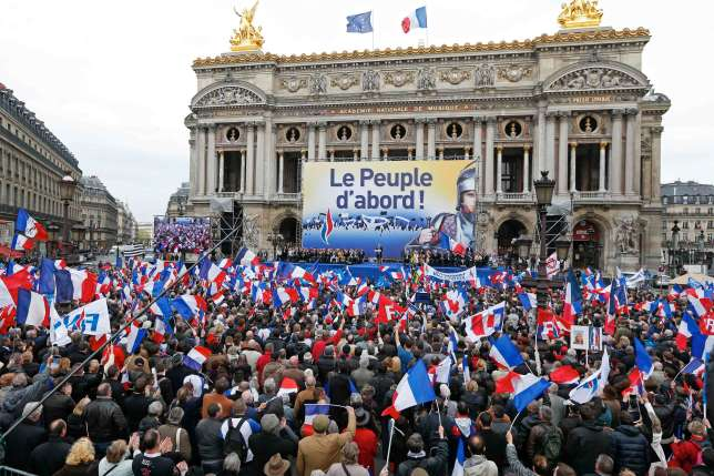 "Supporters of France's National Front political party hold flags and banners as they gather outside the Paris Opera to listen to party head Marine Le Pen at their traditional rally in Paris May 1, 2013. Message reads, ""The People First""."