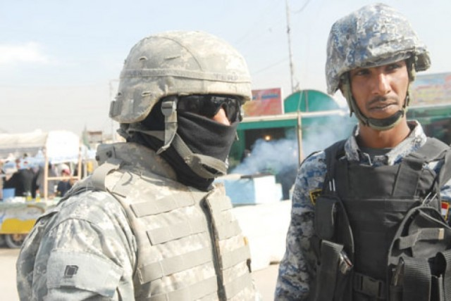 An Iraqi interpreter, left, translates a conversation between an Iraqi National Police officer and U.S. soldiers in Baghdad.