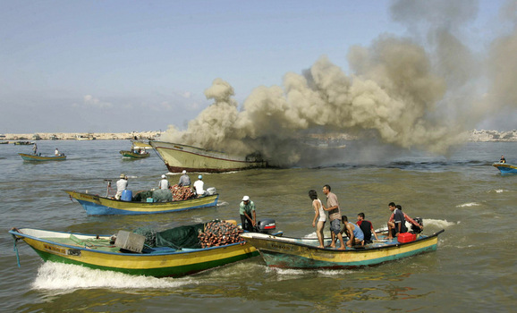Palestinian fishermen gather around a fishing boat after it was hit by Israeli army naval fire at Gaza's seaport
