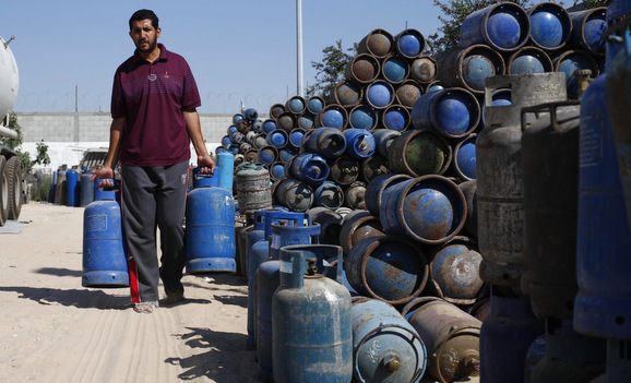 Palestinian man carries cooking gas canisters at a gas filling station in Khan Younis in the southern Gaza Strip