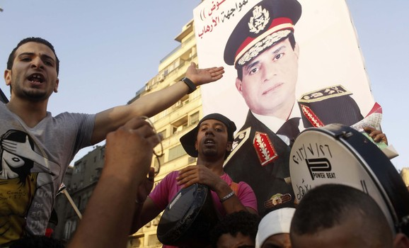 Protesters cheer with drums near a poster of army chief Abdel-Fattah El-Sisi as they gather for a mass protest to support the army in Tahrir square in Cairo