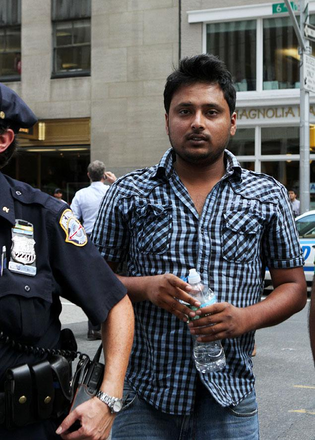 Taxi driver Faysal Kabir Mohammad Himon, 24, of Queens, is accompanied by police on Sixth Ave. after the disaster.