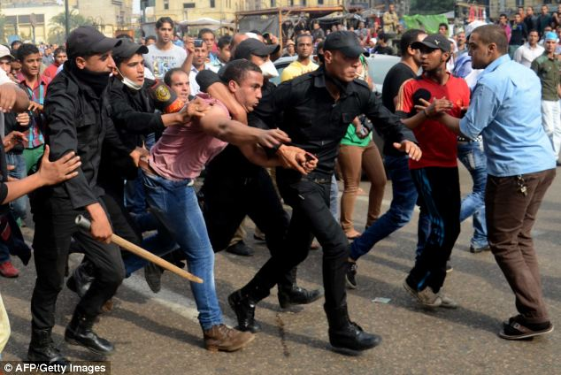 Egyptian policemen arrest a supporter of ousted president Mohamed Morsi during a protest in Ramses Square on the first day of Morsi's trial