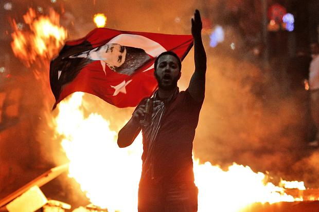 An anti-Erdogan Islamist government protester waves a Turkish flag depicting the founder of modern Turkey Mustafa Kemal Ataturk as thousands of protesters gather in Istanbul's Taksim square, June 9, 2013.