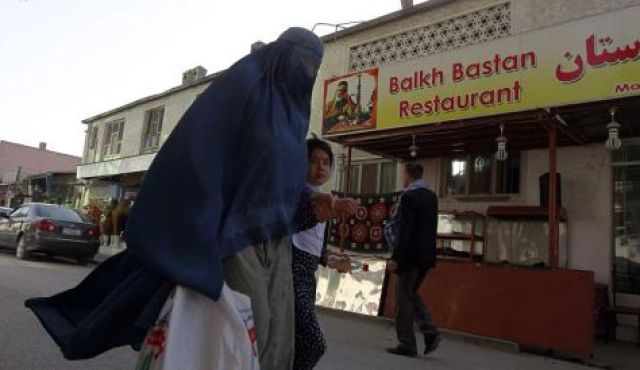 An Afghan woman clad in burqa and her daughter walks past a restaurant built inside part of the only synagogue building in Kabul