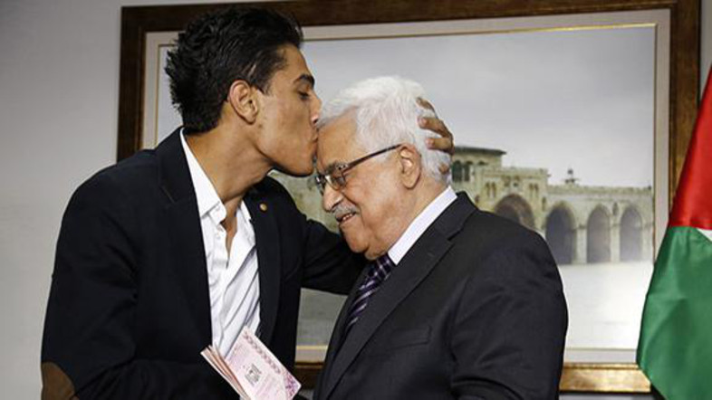 """Arab Idol"" Assaf kisses Palestinian President Abbas as he hands him a diplomatic Palestinian Authority passport during their meeting in Ramallah"