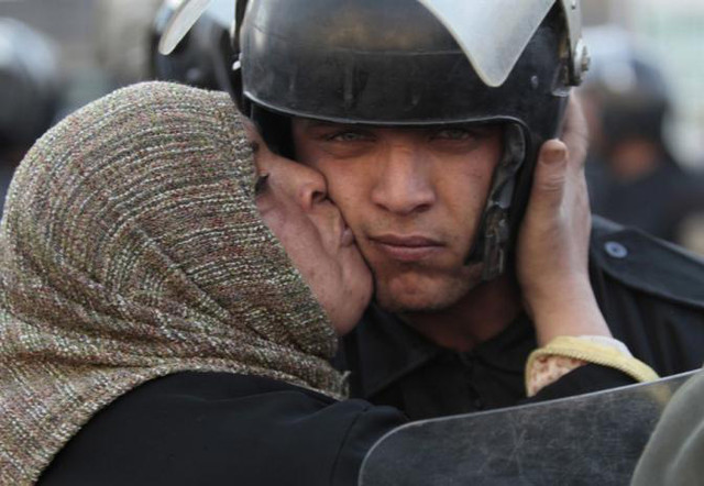 After overthrow of Mohamed Morsi, Egyptians celebrate with National Kissing Day, in which many of the kisses were directed at the Egyptian Army