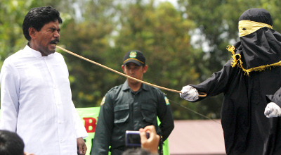 A Sharia law official whips a man convicted of gambling with a rattan cane during a public caning