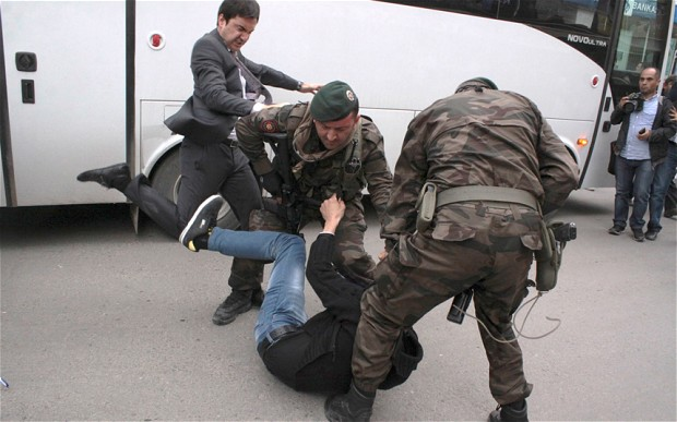 A protester is kicked by Yusuf Yerkel, advisor to Tayyip Erdogan, as Special Forces officers hold him down