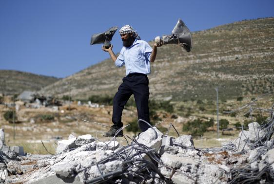 Palestinian man holds damaged loudspeakers belonging to a mosque after it was demolished by Israeli bulldozers in Khirbet Al-Taweel village near the City of Nablus