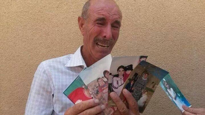 Distraught Yazidi man showing photos of his wife and children who were captured by ISIS