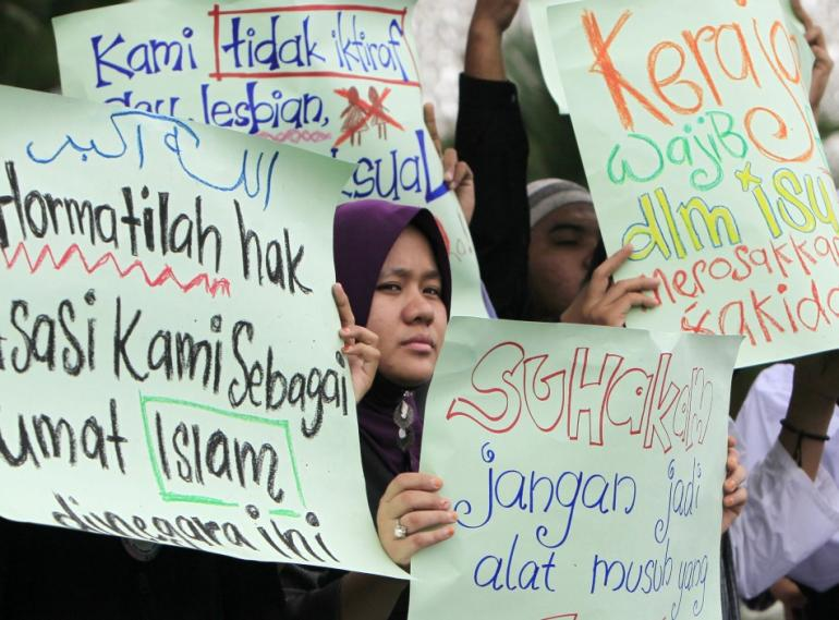 Malaysian Muslims hold placards as they protest against gay rights, outside Kuala Lumpur