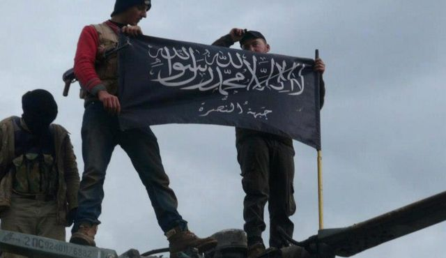 Rebels from Al-Qaeda affiliated Jabhat al-Nusra, wave their brigade flag as they step on the top of a Syrian air force helicopter, at Taftanaz air base, Idlib, Syria, Jan. 11, 2013