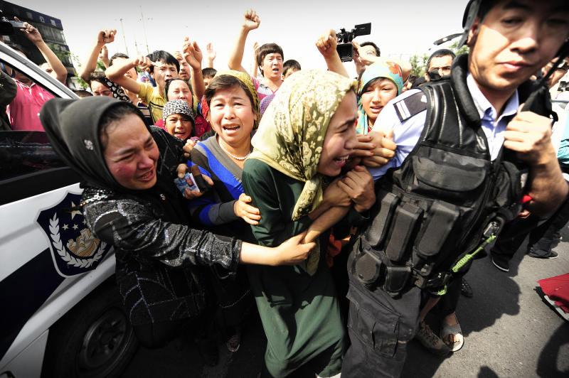 Ethnic Uygur women grab a riot policemen