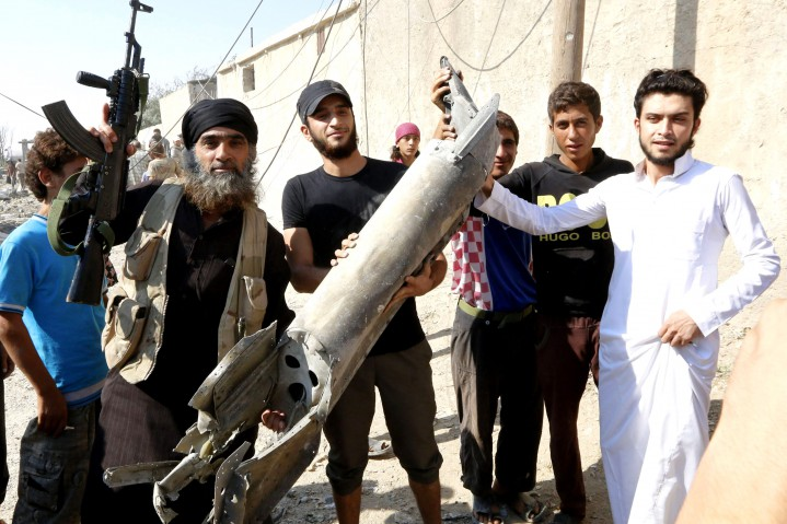 An Islamic State militant (L) stands next to residents as they hold pieces of wreckage from a Syrian war plane after it crashed in Raqqa