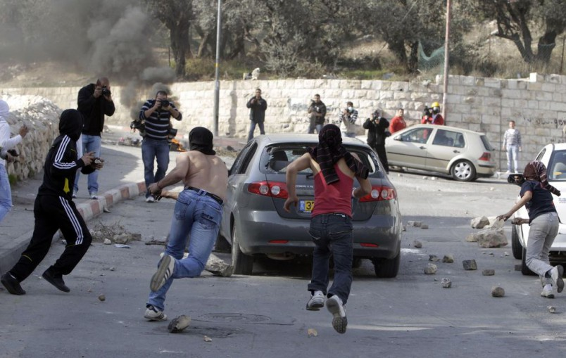 Palestinians throw stones at an Israeli-owned vehicle in the predominantly Palestinian neighbourhood of Silwan in East Jerusalem
