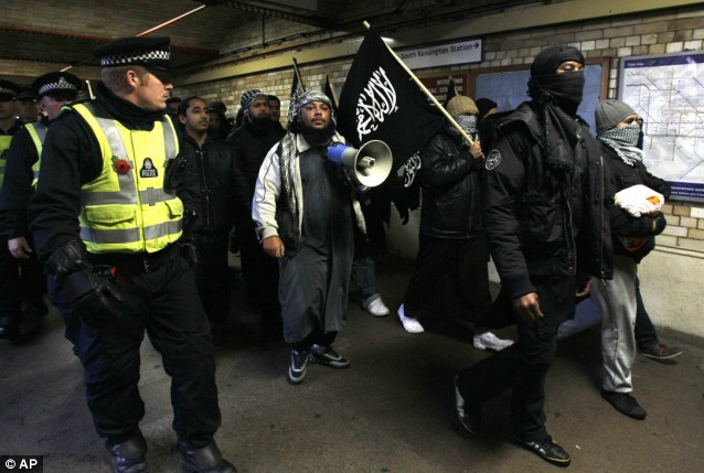 Muslims in London marching with the flag of ISIS as police looks on