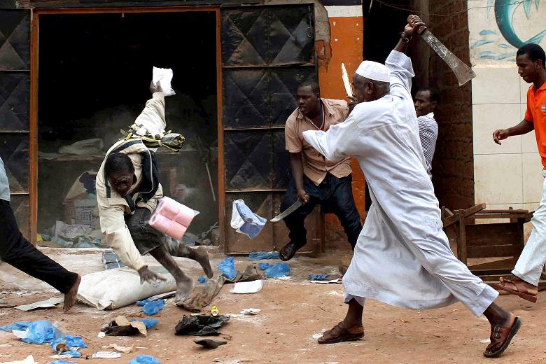 A muslim seeing his store plundered by Christians pursues them with his machete