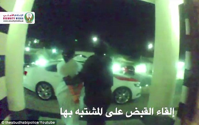 Suspect is seen being led away in cuffs following the night-time raid on her home