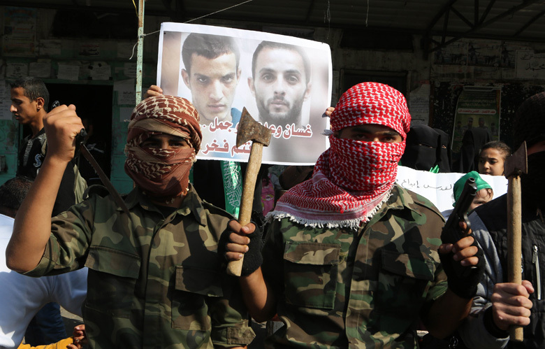 Masked Palestinians hold knifes and axes as they celebrate an attack on a Jerusalem synagogue while standing in front of a poster of the attackers,Ghassan and Uday Abu Jamal