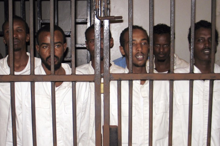 Suspected Somali pirates captured by British Navy officials in the Gulf of Aden stand in a cell at the court in Mombasa