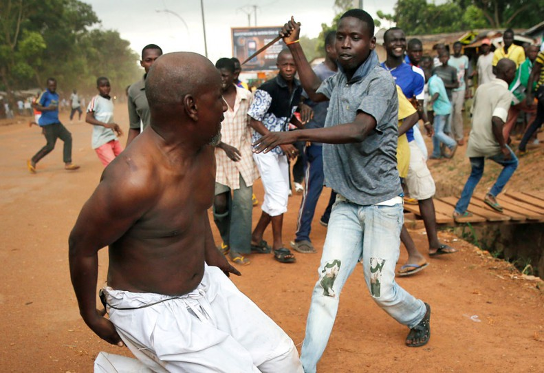 A Christian man chases a suspected Seleka Muslim terrorist in civilian clothes with a knife near the airport in Bangu