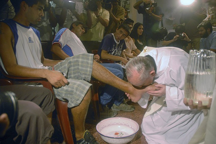 the Pope kisses the foot of a young man in a Roman detention centre