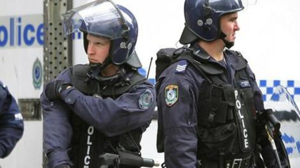 Riot police watch demonstrators protest against the Asia-Pacific Economic Co-operation (APEC) summit from a distance in Sydney