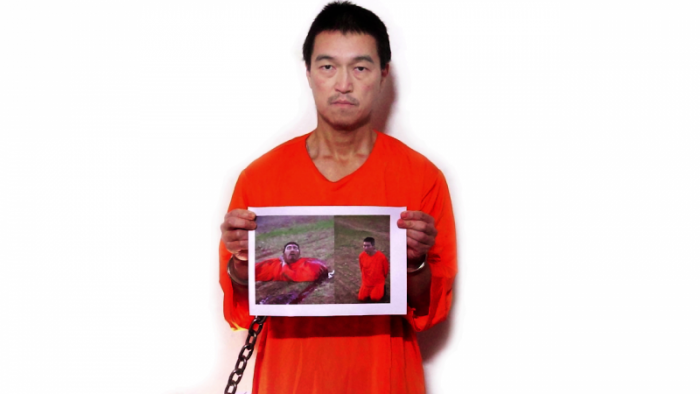 Kenji Goto holding up photo of a beheaded Haruna Yukawa