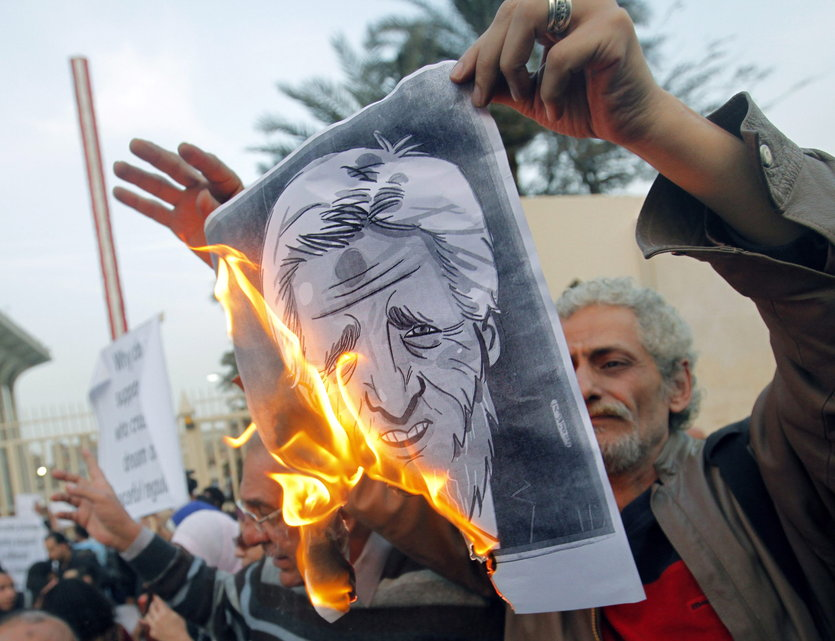 Signs seen in the Egyptian protests against John Kerry included a burning picture of him with a Muslim beard and Islamic prayer bump on his head