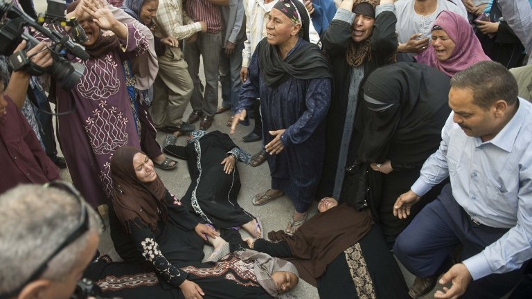 Egyptian women faint outside the courtroom in Egypt's southern province of Minya after an Egyptian court sentenced Muslim Brotherhood spiritual leader Mohamed Badie and others to death,