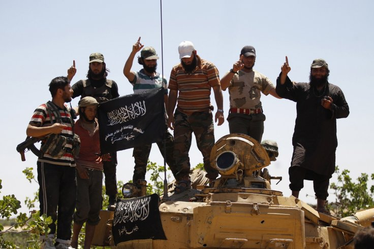 Syrian rebel group Jabhat al-Nusra members pose on a tank in northern Idlib province.
