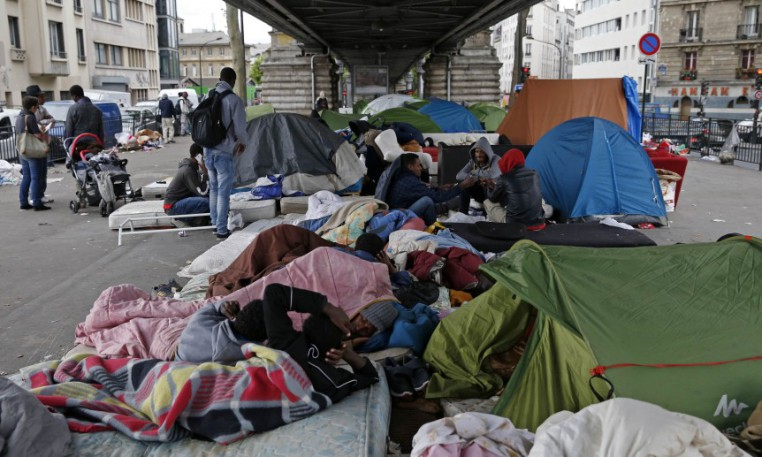 General view of migrants from Eritrea who stand and sit near tents as they live in a make-shift camp under a metro bridge in Paris