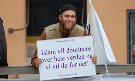 "Smiling Danish Muslim hold sign that says ""Islam will dominate the world"""