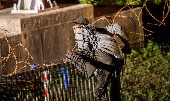 Calais-migrant-climbs-fence-324691