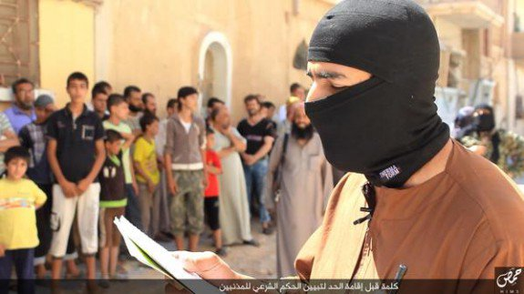 ISIS fighters read their charges to the crowd.