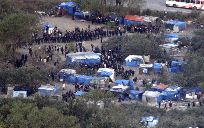 "Police officers surround  makeshift illegals camp known as the ""Jungle"" in Calais"