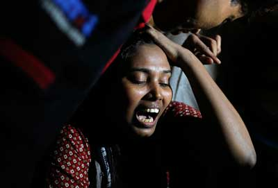 Ashamoni, wife of blogger Niloy Neel, cries at her house in Dhaka Friday.