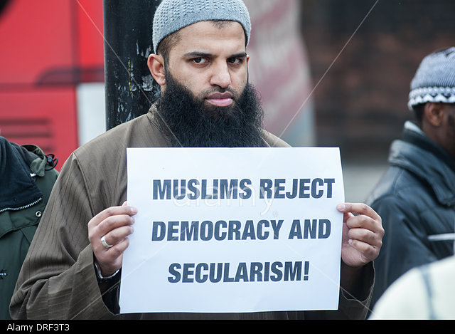 "London, UK. 24th January 2014. Abu Walaa, founder of Muslim Prisoners,holds a placard reading ""Muslims reject democracy and secularism!"" outside the Regents Park Mosque. © Piero Cruciatti/Alamy Live News"