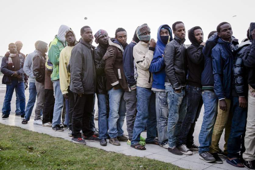 Migrants wait in line for clothes distribution in Calais, France.
