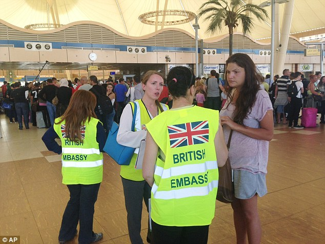 A tourist talks to staff from the British Embassy as other holidaymakers wait at the security gate at Sharm el-Sheikh airport. The evacuation has begun of 20,000 Britons trapped in Egypt after planes were grounded on the orders of David Cameron over fears a Russian jet was blown up by a bomb planted at the airport